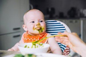baby mit spinat im gesicht