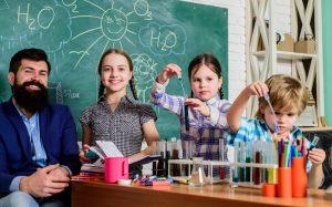 kinder experimentieren gemeinsam mit ihrem lehrer in der klasse