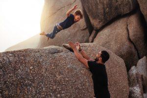 kind springt bei einem vertrauensspiel in die arme seines vaters
