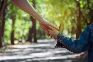 kind haelt die hand eines erwachsenen fest