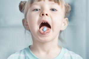 kleines Mädchen mit einer Tablette im Mund