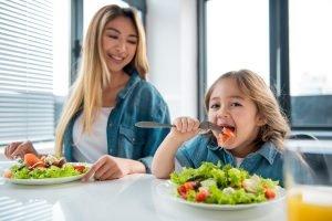 Mutter und Tochter essen gemeinsam je einen bunten Salat
