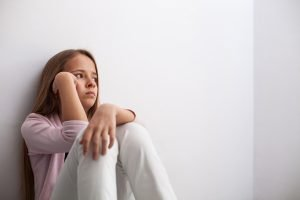 junges teenager-maedchen sitz am boden vor einer weißen wand und denkt nach
