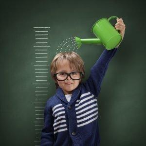 Kind gießt sich mit einer Gießkanne