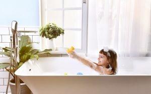 glückliches kleines Mädchen in der Badewanne
