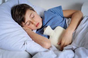 Kind liegt mit einer Wärmflasche im Bett