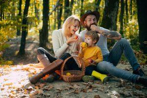 familie sitzt im wald auf dem boden und isst fruechte