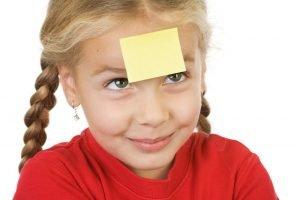 ein kleines Mädchen mit einem Klebezettel auf der Stirn