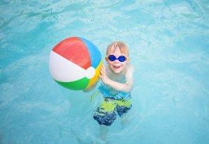 kleines Kind mit einem Wasserball im Schwimmbecken