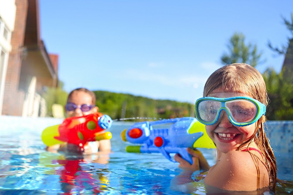 Kinder spielen mit wasserpistolen im pool