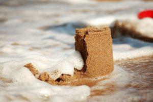 eine sandburg wird von einer welle weggespuelt