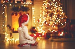 Kleines Mädchen sitzt vor einem Weihnachtsbaum