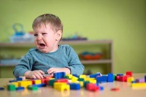 weinendes Kind ist von Bauklötzen umgeben