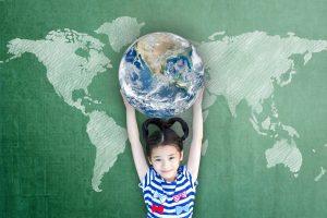 Kind hält eine Weltkugel in die Luft