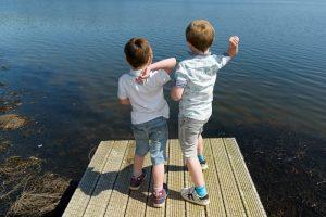zwei Jungs werfen Steine ins Wasser
