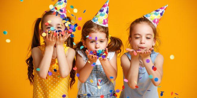 Mädchen mit Partyhüten pusten Konfetti