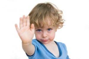 kind zeigt mit der Hand ein Nein an