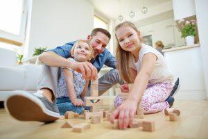 Vater und zwei Kinder spielen mit Bausteinen