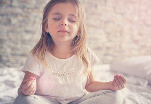 kleines maechen sitzt in yogahaltung auf dem bett