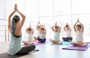 eine frau unterrichtet kinder im yoga