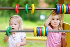 Kinder stehen vor einem großen Rechenschieber