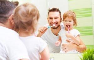 Vater putzt zusammen mit seiner Tochter die Zähne