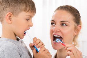 Mutter übt mit ihrem Sohn das Zähneputzen