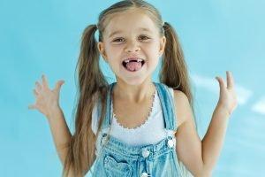 fröhliches, kleines Mädchen mit einer großen Zahnlücke