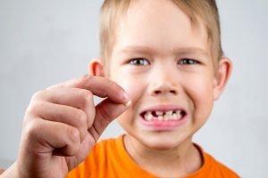 aggressiver Junge hält ausgefallenen Zahn in die Luft