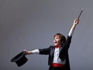 Kind im Zauberoutfit vollführt einen Trick