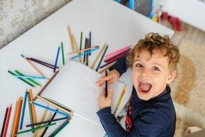 ein Kind ist umgeben von Buntstiften