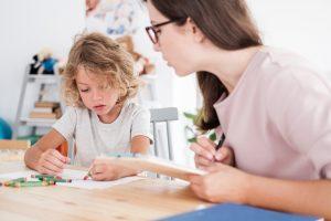 Kind zeichnet unter Beobachtung