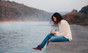 Frau sitzt alleine am See
