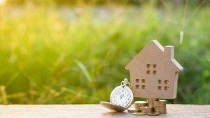 Uhr, Münzen und ein kleines Modell eines Hauses