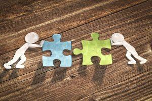 zwei papiermaennchen schieben zwei puzzleteile zusammen
