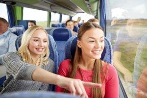 zwei Mädchen sitzen im Bus und schauen nach draußen