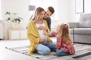 junge schwangere frau mit ihrem mann und ihrem kind zuhause