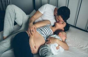 Schwangere Frau küsst ihren Mann, während der Sohn schläft