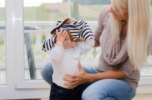 mutter hilft ihrem kind beim ausziehen