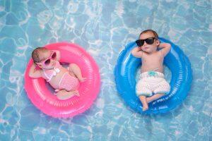 Zwillinge auf Schwimmringen im Pool
